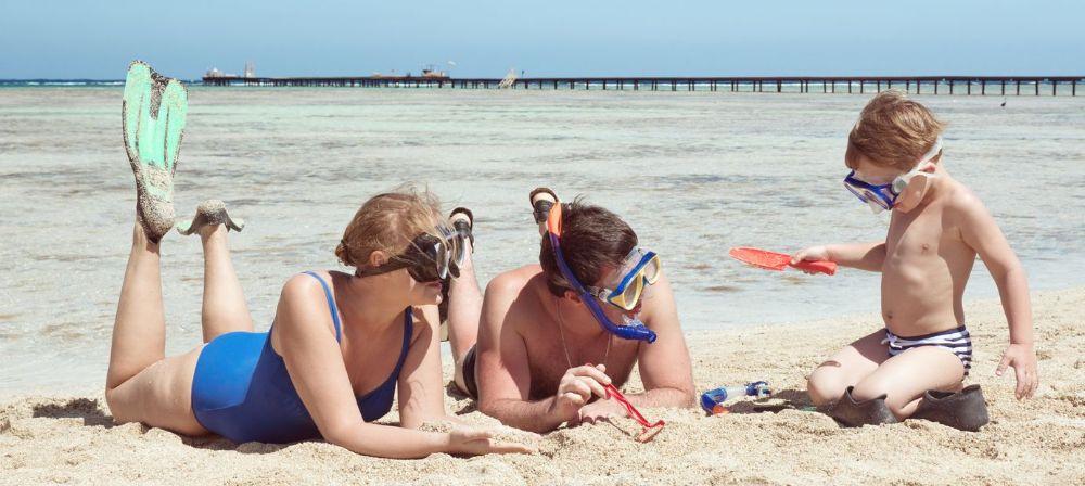 Børn leger på strand iført snorkler, dykkermasker og svømmefødder